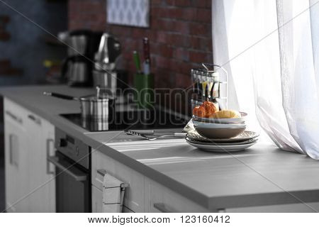 Modern kitchen table with electric stove beside the window