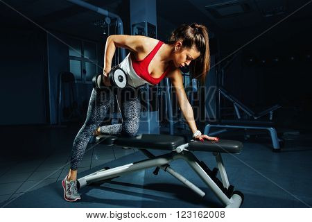 Young woman at the gym back workout with dumbbells
