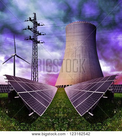 Solar energy panels with nuclear power plant and wind turbines against storm clouds