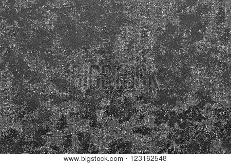 texture of textile fabric with spots from glossy scaly leather of black color for an abstract background or for the textured wallpaper