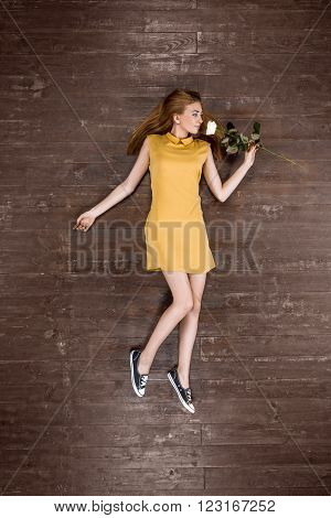 Top view creative photo of beautiful young woman on vintage brown wooden floor. Girl holding rose