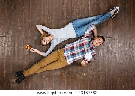 Top view creative photo of beautiful young couple on vintage brown wooden floor. Couple lying with candies