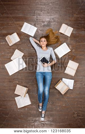Top view creative photo of beautiful young woman on vintage brown wooden floor. Girl lying near books and holding tablet computer