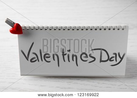Blank present card with small heart on wooden background