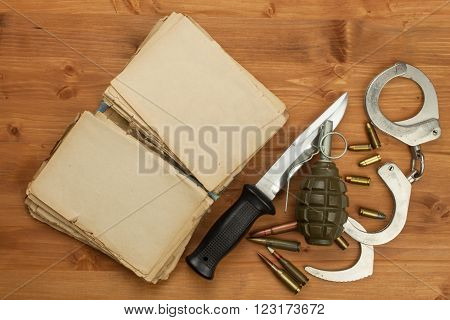 Gun and book crime and punishment. Place for your text. Knife and a book on wooden background.