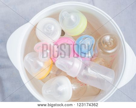 Nipple teethers and milk bottles in steam sterilizer and dryer. Steam sterilizer used for sterilize baby accessories by high temperature steam. poster