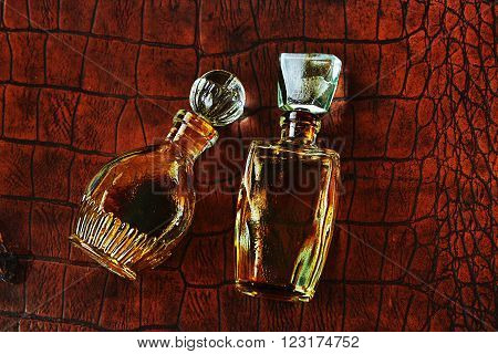 Two vintage perfume on a old leather background