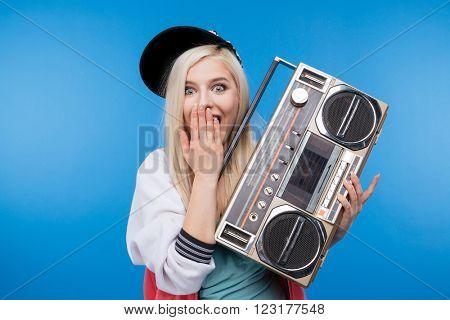 Happy female teenager holding retro boom box on blue background