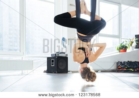 Back view of attractive young woman doing antigravity yoga using hammock in studio