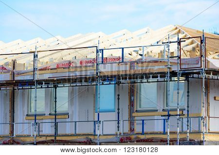 Kristianstad Sweden - March 20 2016: Rafters are in place and the walls are covered in plasterboard. Scaffoldings surround the building.