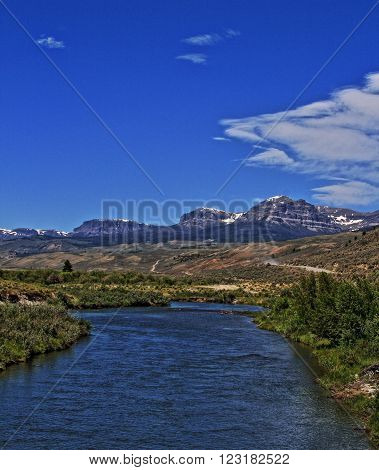 Du Noir Creek in Dubois Wyoming with Breccia Cliffs and Breccia Peak in the background on Togwotee Pass of the Absaroka Mountain Range during the summer in Wyoming USA with wispy cirrus and cumulus clouds over head