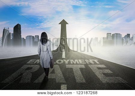 Young businesswoman walking on the road with employment rate text and upward arrow
