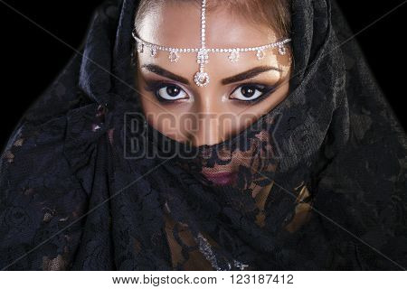 Portrait of a beautiful woman with arabian makeup in black paranja isolated on dark background