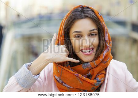 Beautiful brunette woman making a call me gesture. Arab young girl in orange scarf