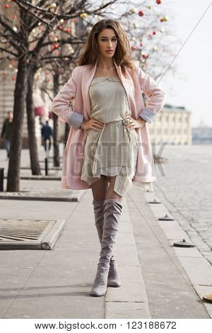 Portrait in full growth, sexy young brunette woman in pink coat