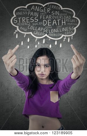 Picture of teenage girl looks angry and shows obscene gesture with middle finger