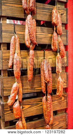 Authentic Italian Pepperoni sausages hanging on a wooded wall