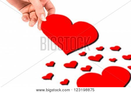 Several hearts on a white background and a hand taking one.