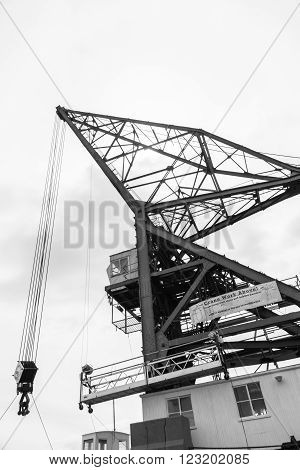 Wellington,New Zealand - February 15, 2016: Large crane projecting skyward from low angle with safety warning sign Crane Work Above in monochrome structural image