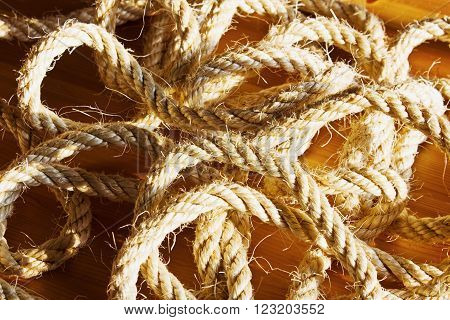 Vintage toned image of hank large ship's rope on the background of a brown wooden table. Hank of twine.
