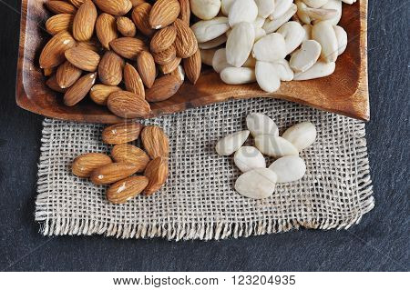 Peeled almonds and blanched Almond on the wood plate. poster