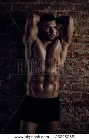 Young muscular man posing near red brick wall