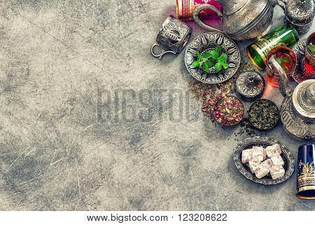 Tea table place setting with colorful glasses. Oriental hospitality concept. Vintage style toned picture