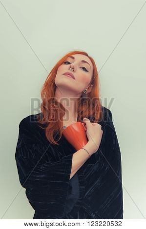 Young redhead woman standing with orange mug