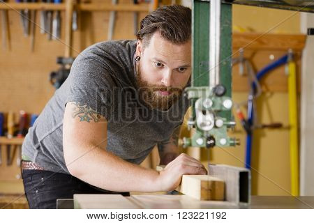 Carpenter using band saw for cutting wood in a work shop for woodwork. Man with tattoo and beard.