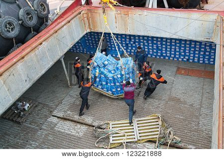 Sea of Okhotsk Russia - October 2th 2014: Sea of Okhotsk the work of team seamens in hold of sea refrigerator ship CRISTAL AFRICA.
