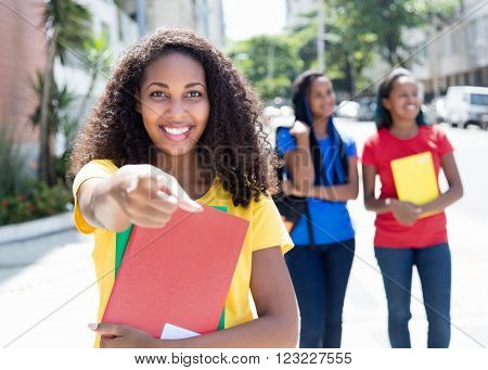 Caribbean student pointing at camera in the city with friends and modern buildings in the background