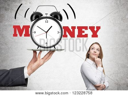 Hand holding alarm clock on tablet businesswoman looking at it. Concrete background. Concept of time is money.