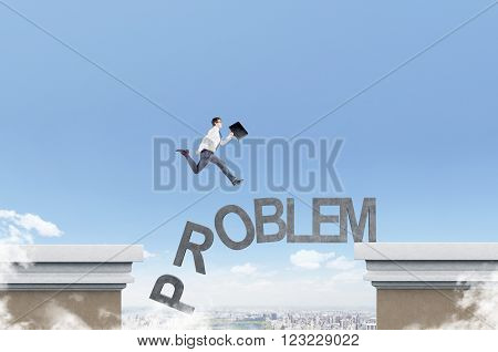 Businessman running over letters of word 'problem' from one roof to another. Blue sky and city at background. Concept of coping with problem.