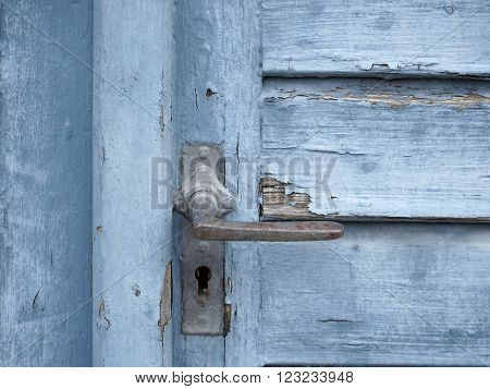 detail of a old rundown blue wooden door with blue flaking paint