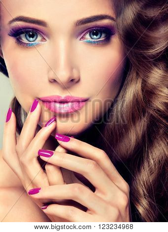 Beautiful girl with long wavy hair.  Brunette  model with curly hairstyle. Cosmetics, makeup and manicure nails.