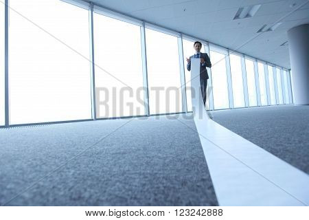 Office worker unrolling long sheet of paper