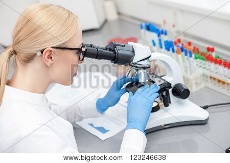 Microbiology can save human life. Professional female scientist is looking at samples through the microscope with concentration. She is sitting at the desk in lab