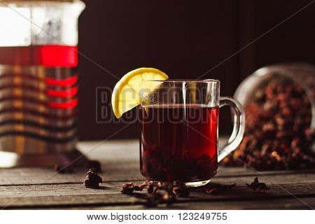A Cup Of Hibiscus Tea From Sudanese Rose With Lemon And Cinnamon Sticks. Brew In Teapot On A Black W