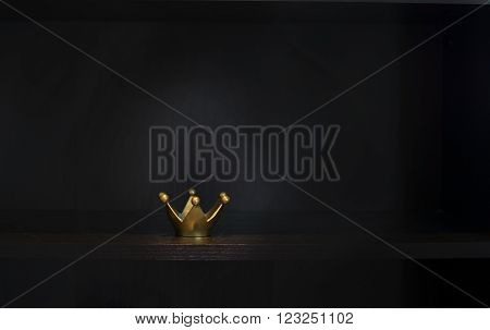 Gold metal crown on dark background with copy space