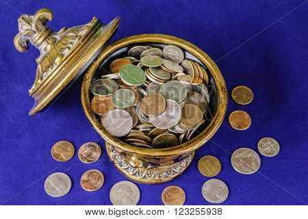 antique vase full of assorted coins on blue background