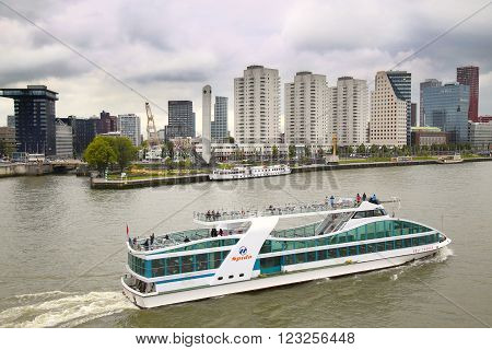 ROTTERDAM THE NETHERLANDS - 18 AUGUST: View from Erasmus bridge on skyline of Rotterdam with a cruise boat river Maas in Rotterdam Netherlands on August 182015.