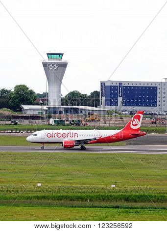 BIRMINGHAM, UK - JUNE 13, 2012 - Air Berlin A320 D-ABDW taxiing after landing with the new control tower to the rear at Birmingham Airport Birmingham England UK Western Europe, June 13, 2012.