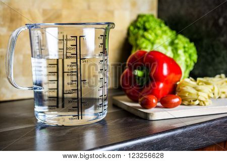 750ccm / 3/4 Liter / 750ml Of Water In A Measuring Cup On A Kitchen Counter With Food