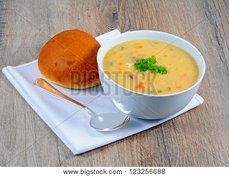 Fish chowder soup including smoked haddock cod salmon and vegetables served with a bread roll.