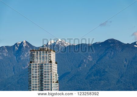 High Rise building against mountain range. Vancouver BC Canada