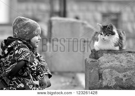 Young girl in pushchair with stray cat in Baku, capital of Azerbaijan. Black and white image showing affection from infant girl towards a long haired stray cat
