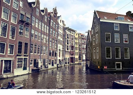 AMSTERDAM, THE NETHERLANDS - AUGUST 19, 2015: View on Oudezijds Kolk canal, street life, bicycle, canal in Amsterdam. Amsterdam is capital of the Netherlands on August 19, 2015.