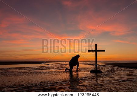A man praying by a black cross with a flowing stream water around it at a beach with the sunset sky.