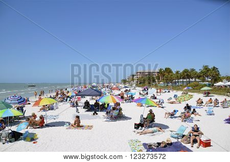 FORT MYERS BEACH, March 14, 2015:FLORIDA - Colorful Atlantic coast beach scene of many people suntanning, relaxing and enjoying the shore and beach during spring break on a hot and sunny, clear blue sky day.