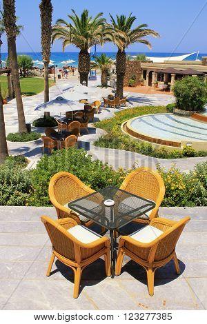 CRETE, GREECE - JULY 23, 2015: Summer view with mediterranean beach hotel resort and al fresco wicker seats on the terrace, Crete, Greece. Vertical view